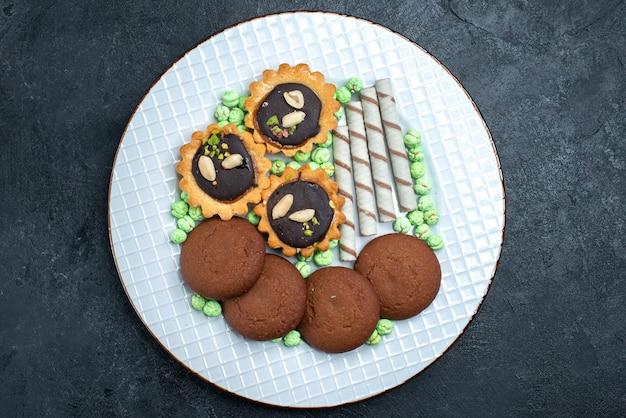 Bovenaanzicht heerlijke koekjes met snoepjes op donkergrijs oppervlak biscuit suiker bak cake taart theekoekje