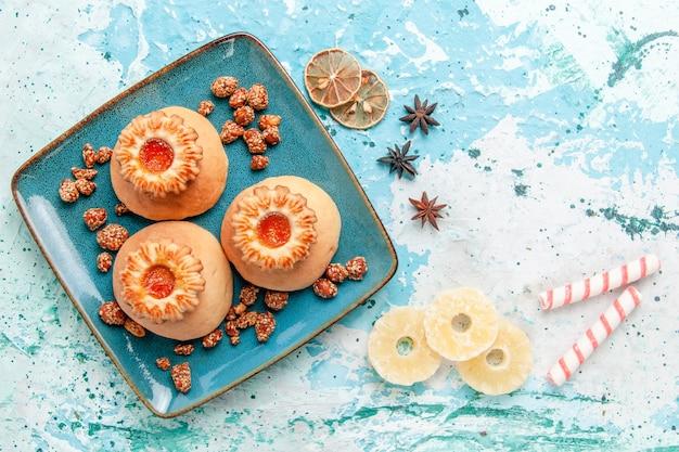 Bovenaanzicht heerlijke koekjes met snoepjes op lichtblauwe oppervlakte cookie biscuit zoete suikerkleur