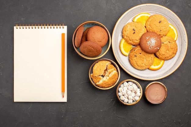 Bovenaanzicht heerlijke koekjes met vers gesneden sinaasappels op donkere achtergrond biscuit fruit zoete cake cookie citrus