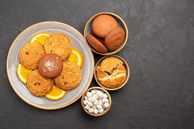 Bovenaanzicht heerlijke koekjes met vers gesneden sinaasappels op donkere achtergrond koekjeskoekje fruit zoete citrus