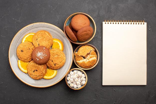 Bovenaanzicht heerlijke koekjes met vers gesneden sinaasappels op een donkere achtergrond koekjes cake fruit zoete citruskoekje