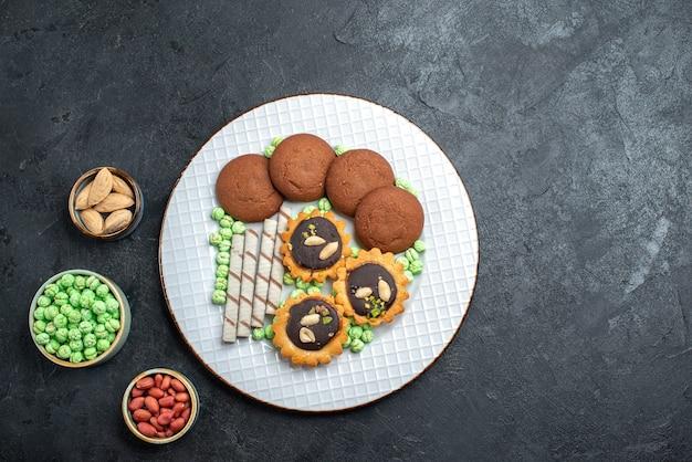 Bovenaanzicht heerlijke koekjes met verschillende snoepjes op donkergrijze achtergrond suiker koekje zoete cake taart thee koekje
