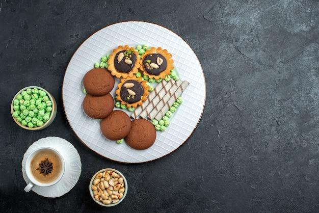 Bovenaanzicht heerlijke koekjes met verschillende snoepjes op donkergrijze achtergrond suikerkoekje zoete cake taartkoekje