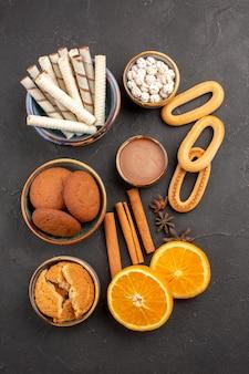 Bovenaanzicht heerlijke koekjes met verse sinaasappels op donkere oppervlaktekoekje zoete citruskoekje fruitsuiker
