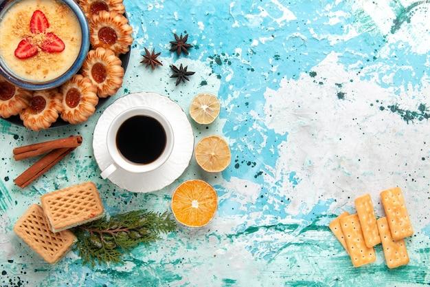 Bovenaanzicht heerlijke koekjes met wafels, koffie en aardbeiendessert op blauw bureau