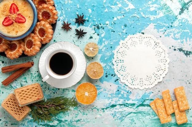 Bovenaanzicht heerlijke koekjes met wafels, koffie en aardbeiendessert op blauwe ondergrond