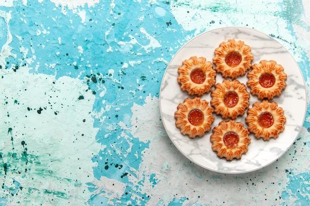 Bovenaanzicht heerlijke koekjes ronde gevormd met jam in plaat op de lichtblauwe achtergrond koekjes suiker zoete biscuit deeg cake bakken
