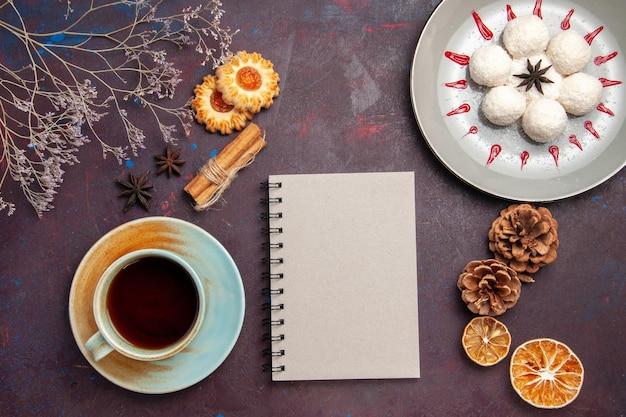 Bovenaanzicht heerlijke kokossnoepjes klein en rond gevormd met kopje thee op donkere achtergrond kokosnoot snoep zoete cake cookie