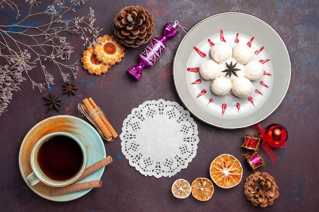 Bovenaanzicht heerlijke kokossnoepjes klein en rond gevormd met kopje thee op donkere achtergrond kokosnoot snoep zoete cake koekjesthee