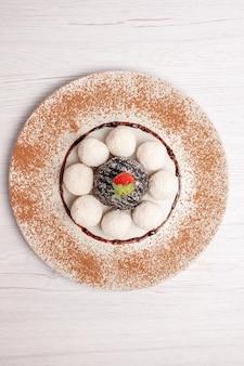 Bovenaanzicht heerlijke kokossnoepjes met chocoladetaart op een wit bureaucake-koekje, zoet snoepkoekje