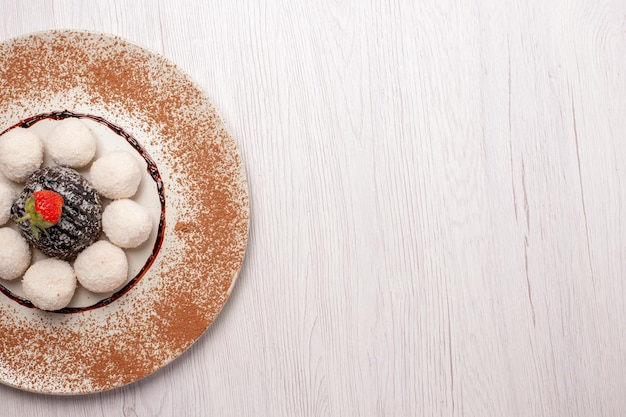 Bovenaanzicht heerlijke kokossnoepjes met chocoladetaart op het witte bureau sugar cake biscuit zoete snoepkoekjes