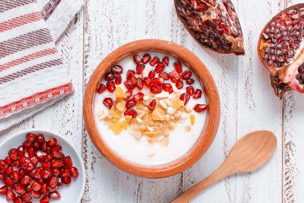 Bovenaanzicht heerlijke kom met melk en granaatappel zaden