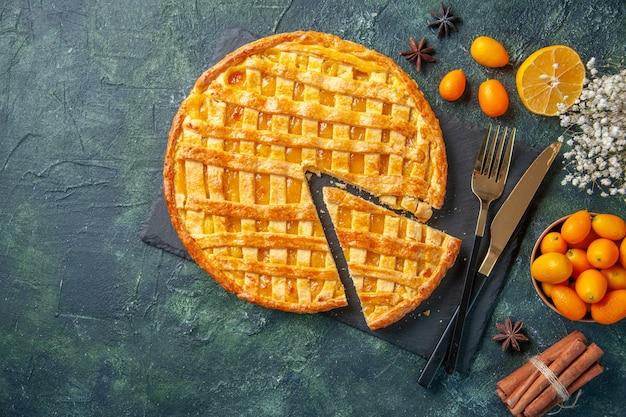Bovenaanzicht heerlijke kumquat-taart met één stuk gesneden op donkere achtergrond