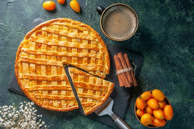 Bovenaanzicht heerlijke kumquat-taart met gesneden een stuk en koffie op donkere achtergrond