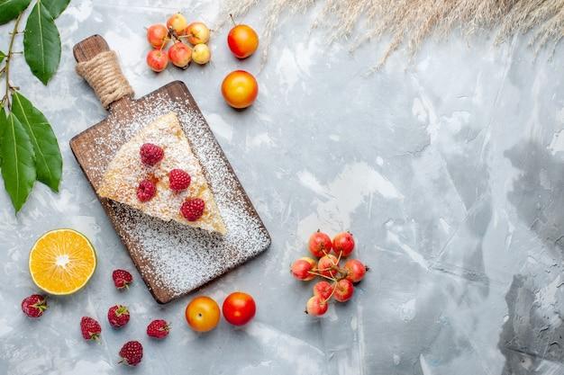 Bovenaanzicht heerlijke lekkere taartschijf met fruit op het witte koekje van de bureausuiker