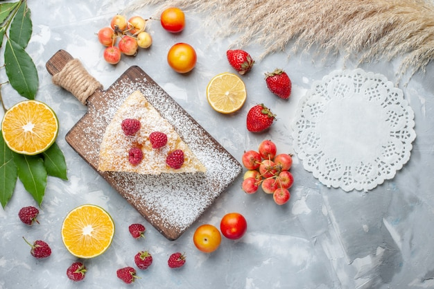 Bovenaanzicht heerlijke lekkere taartschijf met fruit op lichte achtergrond suiker zoete taart cake koekje