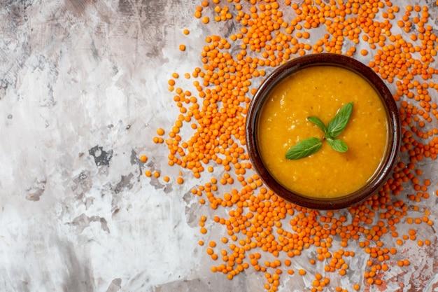 Bovenaanzicht heerlijke linzensoep in bord op een lichte ondergrond plantensoep kleurenfoto voedselzaadschotel