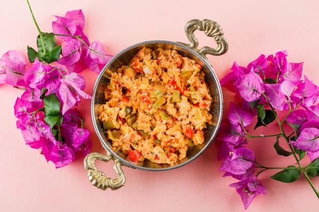 Bovenaanzicht heerlijke maaltijd in pot met bloemen op roze oppervlak