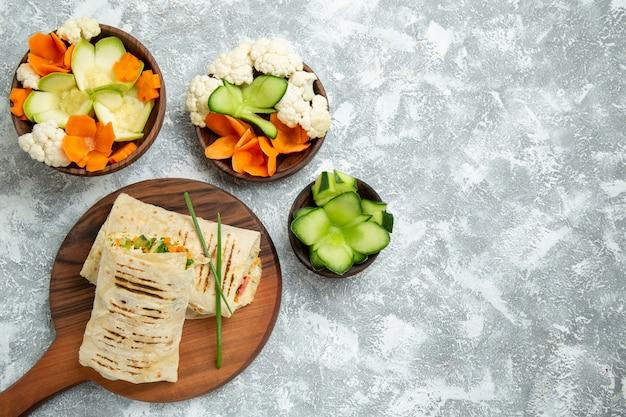 Bovenaanzicht heerlijke maaltijd sandwich met gegrild vlees gesneden met salade op wit bureau