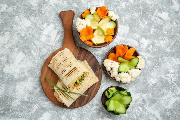 Bovenaanzicht heerlijke maaltijd sandwich met gegrild vlees gesneden met salade op witte ruimte