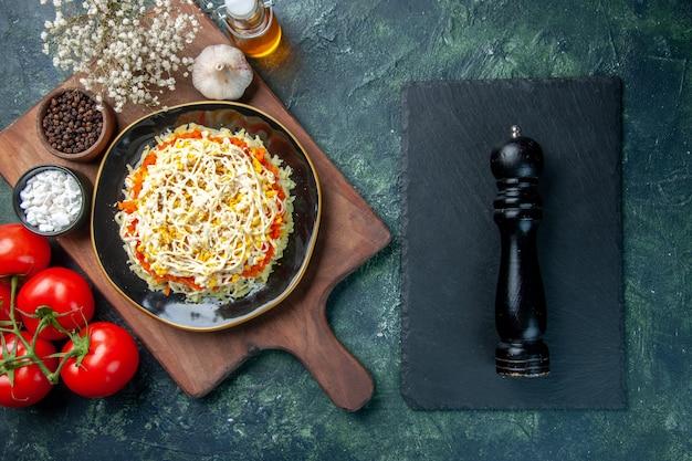 Bovenaanzicht heerlijke mimosa salade binnen plaat met rode tomaten op donkerblauwe achtergrond