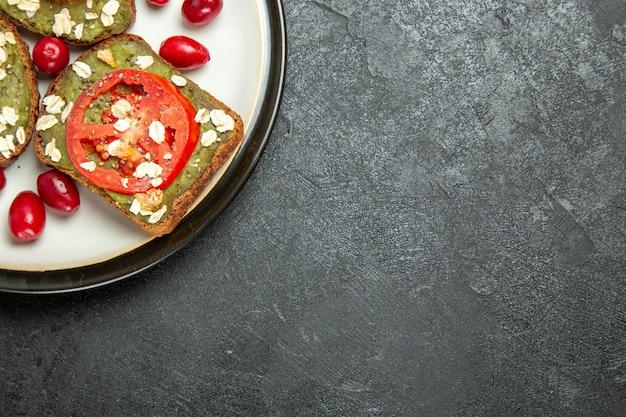 Bovenaanzicht heerlijke nuttige sandwiches met avocado pasta en tomaten in plaat op grijze achtergrond hamburger sandwich brood snack