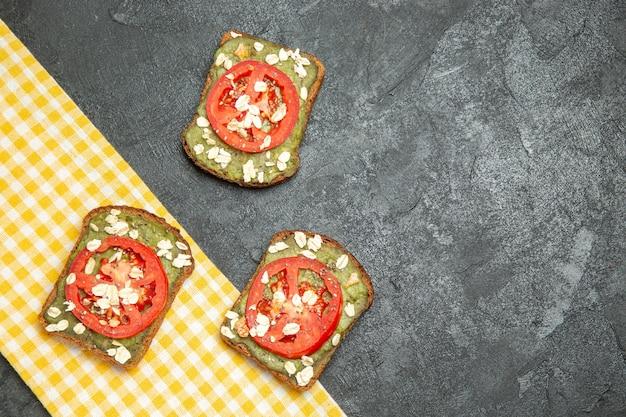 Bovenaanzicht heerlijke nuttige sandwiches met avocado pasta en tomaten op een grijze achtergrond sandwich hamburger brood broodje snack