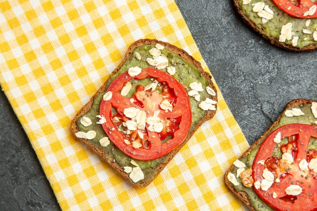 Bovenaanzicht heerlijke nuttige sandwiches met avocado pasta en tomaten op grijze ondergrond sandwich hamburger brood broodje snack