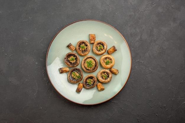 Bovenaanzicht heerlijke paddenstoelenmaaltijd gekookt met greens in plaat op het donkere oppervlak schotel diner wilde rijpe maaltijd koken