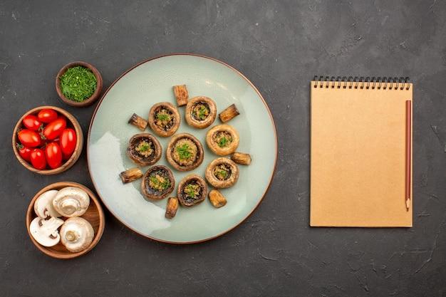 Bovenaanzicht heerlijke paddenstoelenmaaltijd met verse groenten en tomaten op donkergrijze oppervlakteschotel dinermaaltijd kokende paddestoel