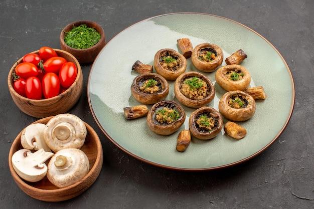 Bovenaanzicht heerlijke paddenstoelenmaaltijd met verse groenten en tomaten op een donkere vloerschotel dinermaaltijd kokende paddestoel