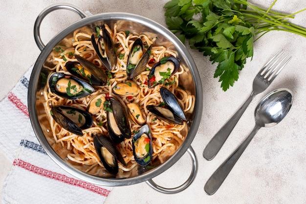 Bovenaanzicht heerlijke pan met pasta en mosselen