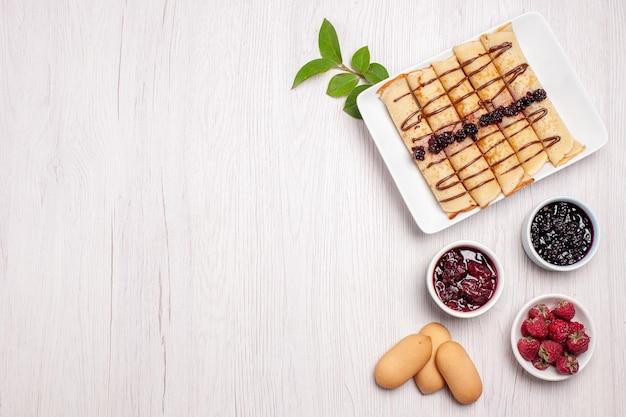 Bovenaanzicht heerlijke pannenkoek broodjes met jam en koekjes op witte achtergrond biscuit cookie cake jam gelei