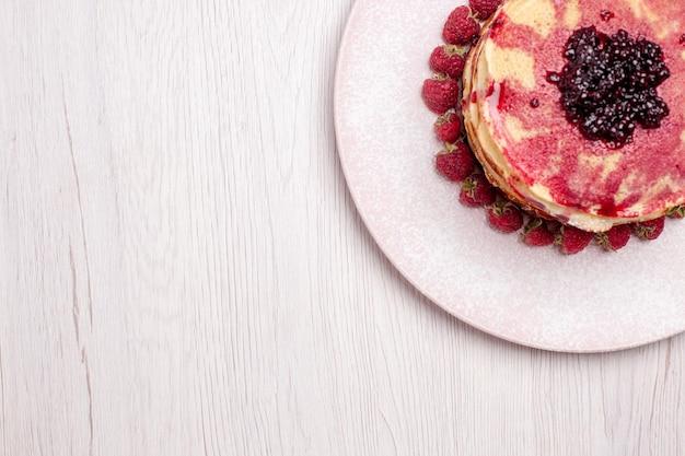 Bovenaanzicht heerlijke pannenkoeken met aardbeien en gelei op een witte taartkoekje met zoete bessenvruchtencake