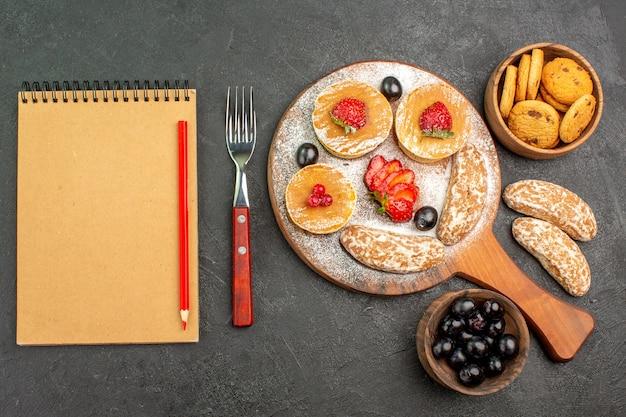 Bovenaanzicht heerlijke pannenkoeken met fruit en zoete taarten op donkere ondergrond cakedessert