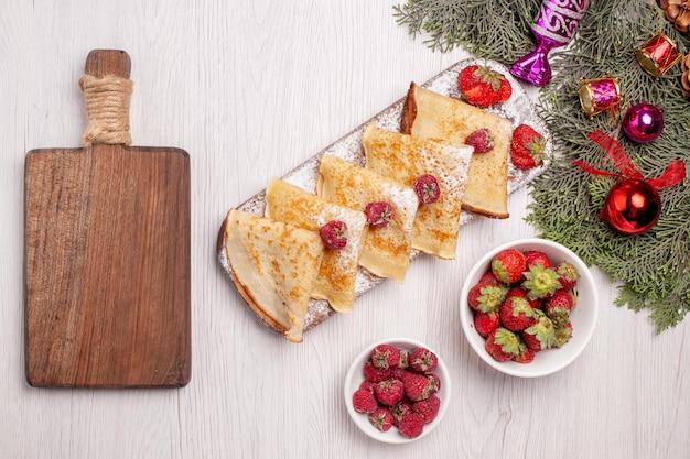 Bovenaanzicht heerlijke pannenkoeken met fruit op witte achtergrond zoete cake dessert fruit thee pannenkoek
