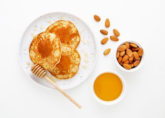 Bovenaanzicht heerlijke pannenkoeken met honing en amandelen