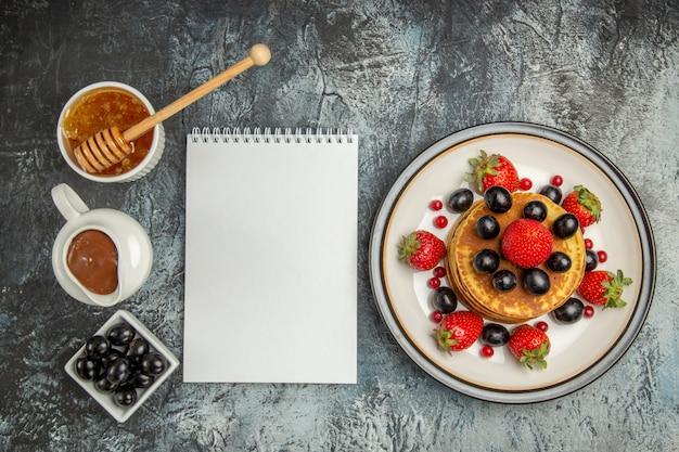 Bovenaanzicht heerlijke pannenkoeken met honing en fruit op lichte zoete fruitcake op de vloer