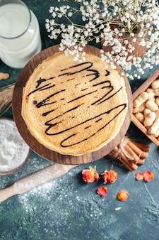 Bovenaanzicht heerlijke pannenkoeken met melk en noten op donkerblauw oppervlak