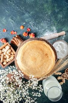 Bovenaanzicht heerlijke pannenkoeken met melk op een donkerblauwe ondergrond