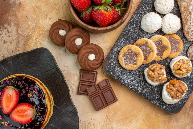 Bovenaanzicht heerlijke pannenkoeken met snoep en koekjes op een houten bureau