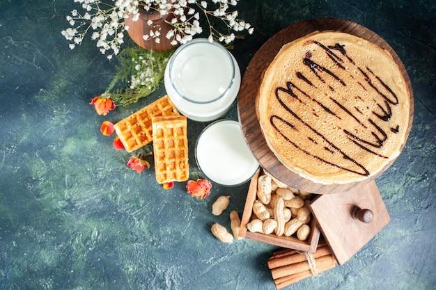 Bovenaanzicht heerlijke pannenkoeken met verse melk en noten op donkerblauw oppervlak