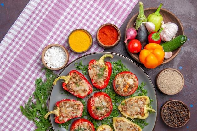 Bovenaanzicht heerlijke paprika smakelijke gekookte maaltijd met vlees en groenten op de donkere achtergrond pittige maaltijd diner schotel peper eten