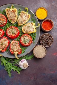Bovenaanzicht heerlijke paprika smakelijke gekookte schotel met vlees en kruiden op donkere achtergrond dinerschotel peper eten pittig