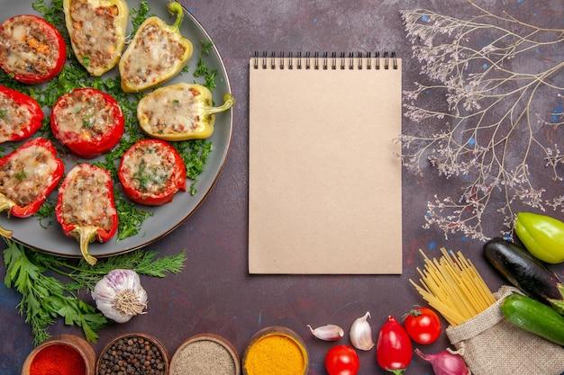 Bovenaanzicht heerlijke paprika smakelijke gekookte schotel met vlees en kruiden op donkere bureauschotel peper diner eten pittig