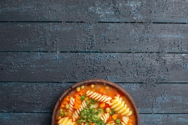 Bovenaanzicht heerlijke pastasoep met groenten en fruit in de plaat op de donkere bureauschotel italiaanse pastasoep dinersaus