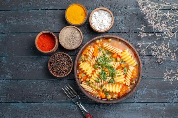 Bovenaanzicht heerlijke pastasoep met groenten en smaakmakers op een donkerblauw bureau dinerschotel italiaanse pastasaussoep