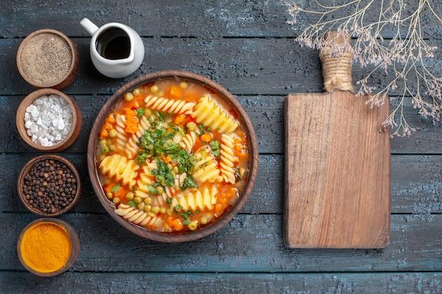 Bovenaanzicht heerlijke pastasoep van spiraalpasta met smaakmakers op de donkerblauwe bureausaus keukenschotel italiaanse pastasoep