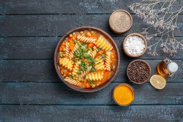 Bovenaanzicht heerlijke pastasoep van spiraalpasta met smaakmakers op donkerblauwe vloersaus keukenschotel italiaanse pastasoep