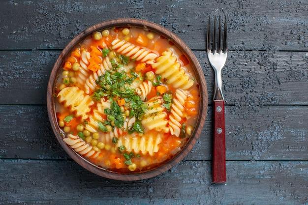 Bovenaanzicht heerlijke pastasoep van spiraalvormige italiaanse pasta met greens op het donkere bureau dinerschotel italiaanse pastasoepsaus